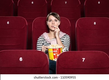 Young girl at the cinema watching a movie