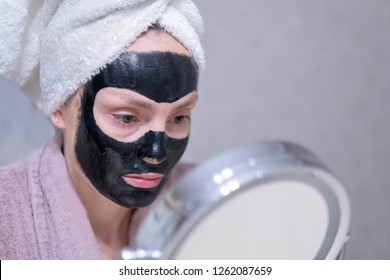 Young girl in a cleansing black coal mask on her face. Black coal exfoliating mask for the face. Black mask deep cleansing. Peel off face mask, blackhead removal,