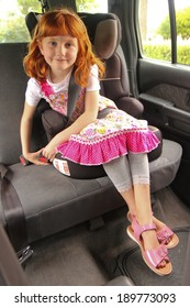 young girl clicking shut her seat belt in a child restraint seat in the back of a car