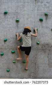 Young girl climbing up the wall
