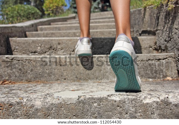 Young girl climbs on concrete stairs