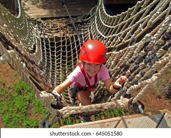 Young girl climbs on a high ropes course