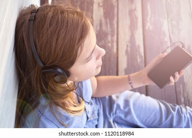 Young girl with closed eyes enjoying music outdoors with earphones and a smartphone