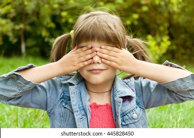 young girl closed her eyes with her hands. concept