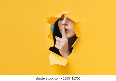 A young girl closes her lips with her index finger,making it clear to the viewer that you need to observe silence,keep a secret and not say too much. ?ensorship and harassment of freedom of speech.