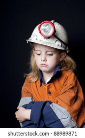 Young girl in coal miner hard hat and safety clothing, looking sad, Black background