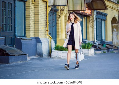 A young girl in a coat and carrying a bag in her hands is walking along the street of the old city.