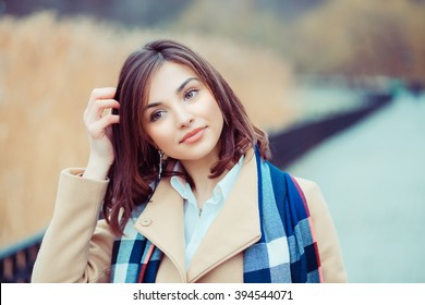 Young girl in coat looking away. Closeup portrait headshot of beautiful stylish smiling  fixing hair, scratching head girl student isolated cityscape  park lake background.  Multicultural, mixt race