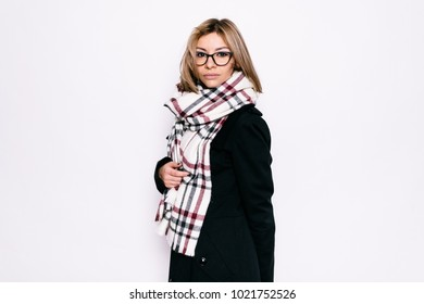 Young girl in a coat with a scarf and glasses on a white background
