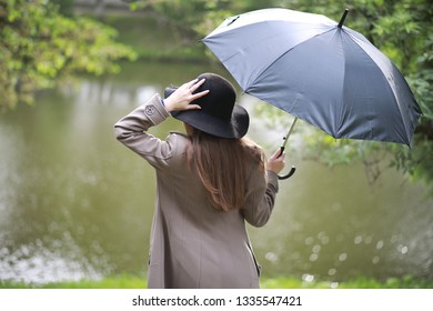 Young girl in a coat in a spring park in the rain