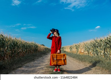 Young girl in coat with suitcase and binoculars on a rural road near cornfield.