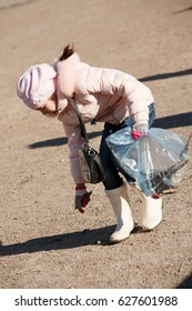 A young girl collects garbage on the side of the road to do your share for the assistance of ecology and environmental protection.