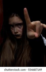 Young girl with colored face pointing by finger