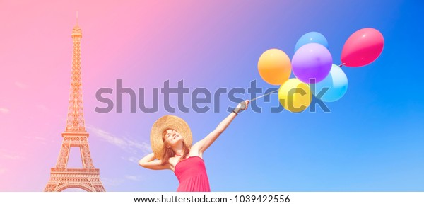 Young girl with colorful balloons on blue sky and Eiffel tower backgorund. Spring or summertime travel concept