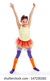 Young girl in Colorful cloths. Funky, quirky and trendy. Holding arms up high and wearing sunglasses with leg warmers.