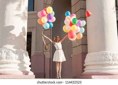 Young girl with colorful latex balloons keeping her dress, urban scene, outdoors