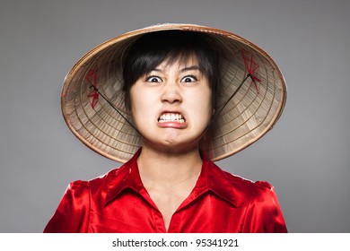 A young girl comically angry with traditional Asian hat
