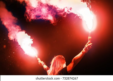 Young girl in a concert crowd holds smoke bombs with fire in their hands