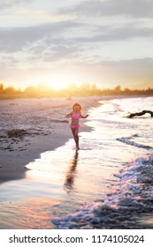 young girl in a costume is playing on the beach