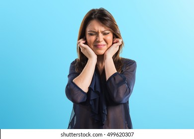 Young girl covering her ears on blue background