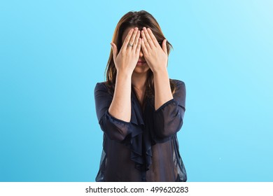 Young girl covering her eyes on blue background