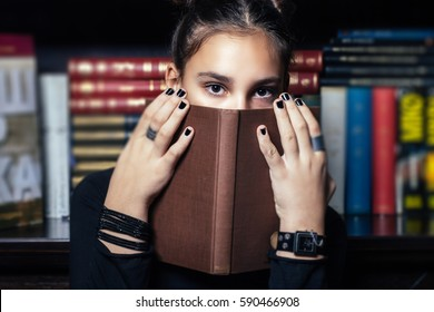 Young girl covering her mouth with book in a book store