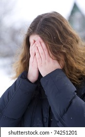 Young girl covering his face by hands