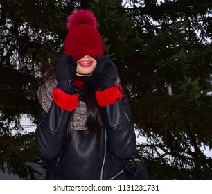 Young girl covers her face with a red hat on a green pine background