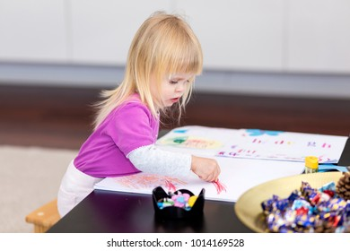 Young girl with a crayon drawing.