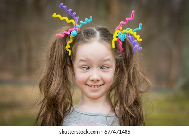 Young girl with crazy hair making faces cross eyed