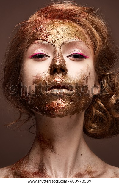 Young girl with creative makeup and textures on her face. Beautiful model with raspberry arrows and golden pigment. Photo is taken in the studio. Beauty of the face