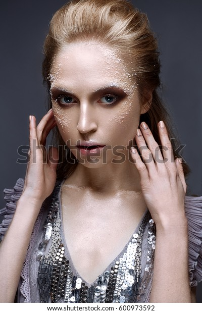 Young girl with creative makeup and textures on her face. Beautiful model in a lilac dress with sparkles. Photo is taken in the studio. Beauty of the face.