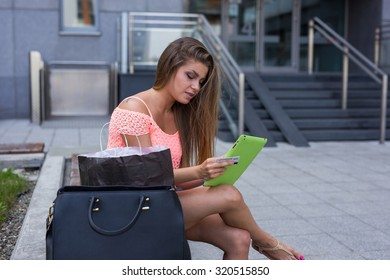 Young girl with credit card and tablet shopping online