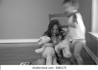 young girl crying with baby brother in action next to her