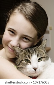 Young girl cuddles her pet cat