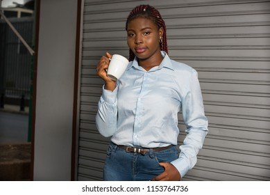 Young girl with a cup of coffee stands on the street next to the business center. Businesswoman drinks hot and invigorating drink at night after work