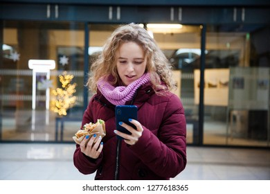 Young girl with curly hair holding a phone in her hands and eating a burger on the street