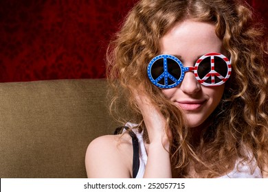 Young girl with curly hair wearing sunglasses with the American flag and a sign of peace.