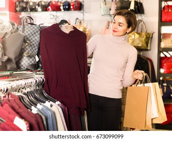 Young girl customer is deciding on warm sweater in womens cloths shop.