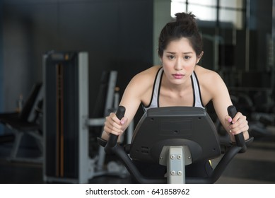 Young girl cycling in the gym. Motivation concept
