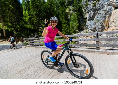 Young girl cycling on bridge along river in Dolomites, Italy