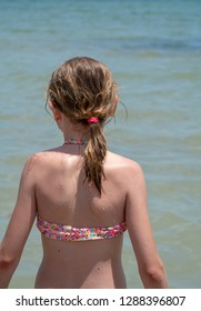 Young girl with damp blond hair tied up in a pony tail stands in the calm sea. Her pink bikini matches a red hair band (scrunchy). Her skin is wet and cooled by water droplets causing goosebumps.
