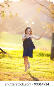A young girl dancing in a field.  There is haze in the background.