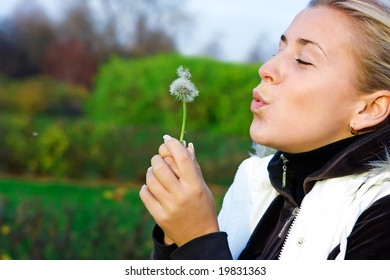 Young girl and dandelion in the countryside