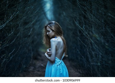 young girl in a dark forest. bare shoulder