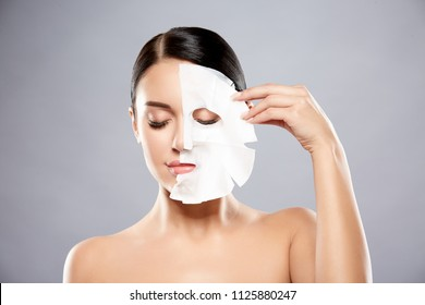 Young girl with dark hair, big eyes, dark eyebrows and naked shoulders looking at camera, a model with light nude make-up, gray studio background, taking off facial mask.