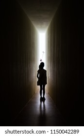 Young girl in dark room walking to the light