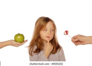 Young girl deciding between apple and sucker (looking at sucker)