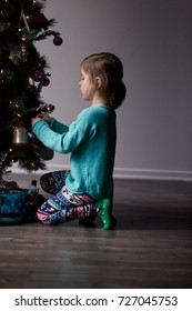 A young girl with is decorating a Christmas tree and is happily playing with the decorations.