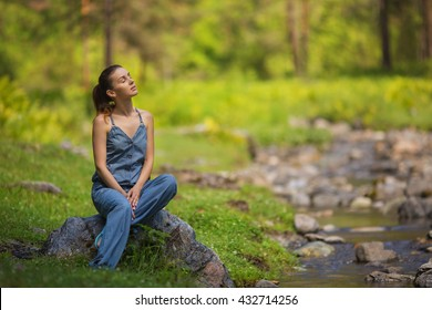 Young girl in a denim dress sits on a stone near a stream in a forest